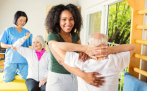 caregiver smiling while conducting physical theraphy