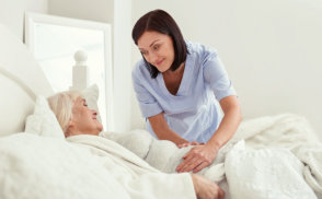 caregiver looking at the senior woman while smiling