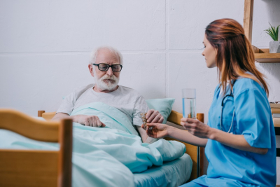 nurse and senior man shaking hands