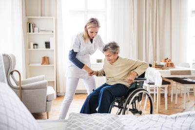 caregiver assisting senior woman to stand
